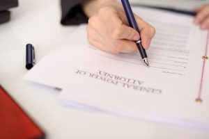 person filling out a power of attorney document